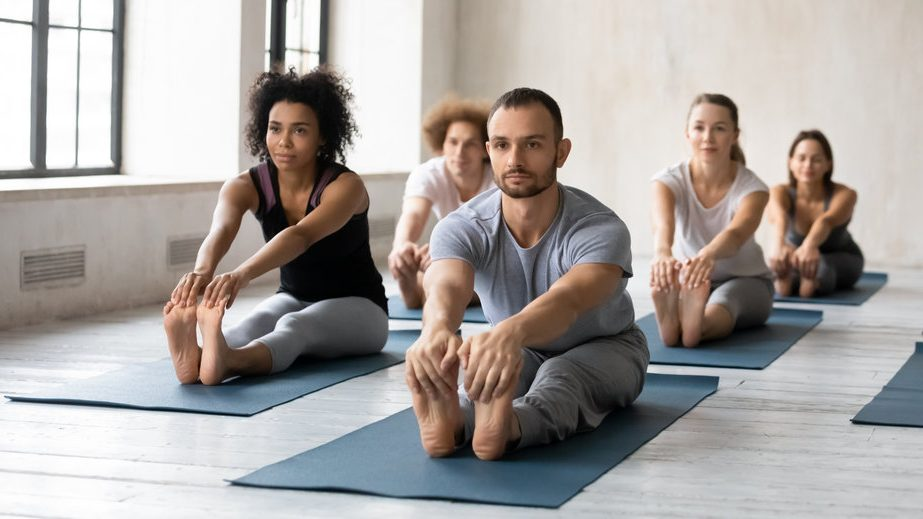 Male and female multiracial people practicing beginner yoga exercises, stretching muscles in seated forward bend pose, focused students in activewear doing paschimottanasana barefoot on floor mat.