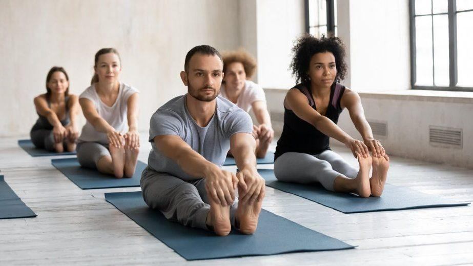 Praktijk de Balans - Male and female multiracial people practicing beginner yoga exercises, stretching muscles in seated forward bend pose, focused students in activewear doing paschimottanasana barefoot on floor mat.